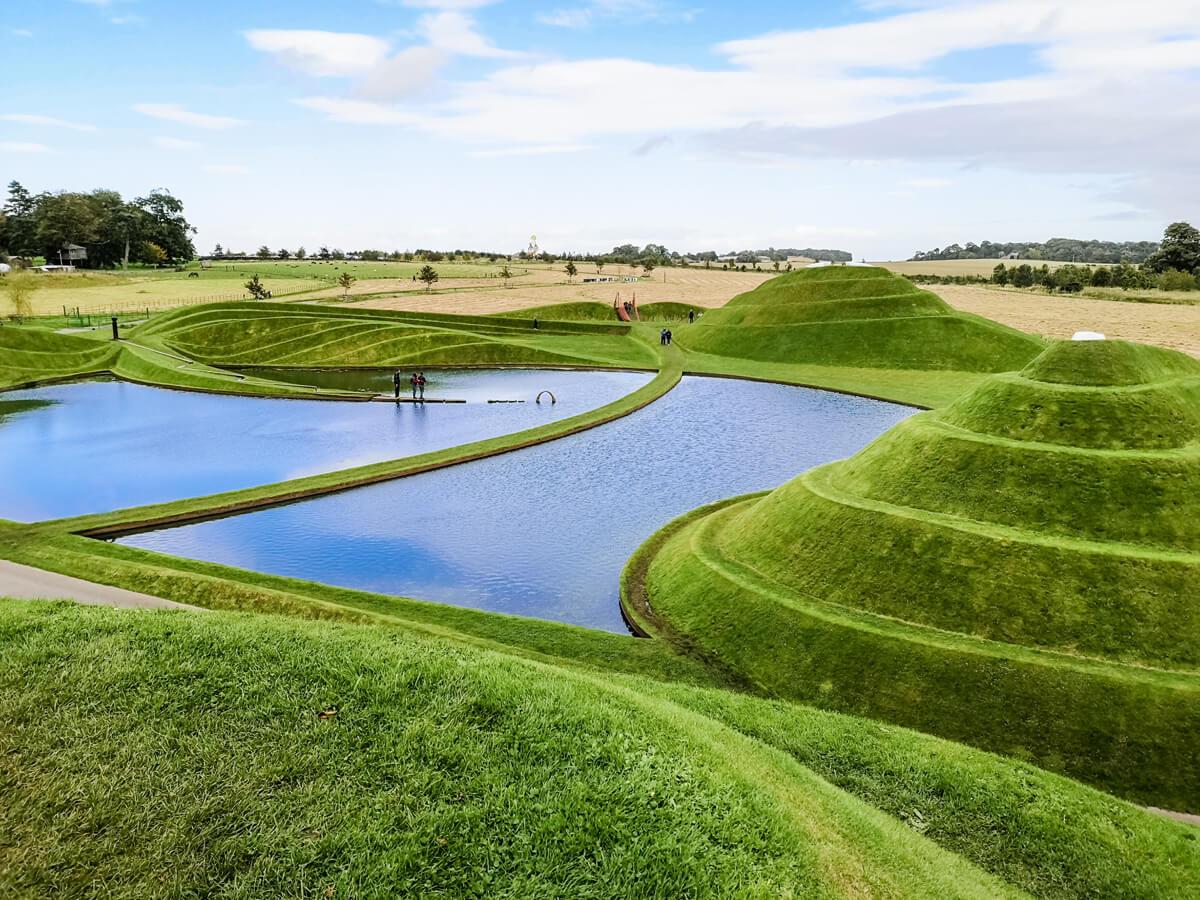 An overlooking shot of Jupiter Artland Edinburgh sculpture park taken from the top of the the grass mounds.