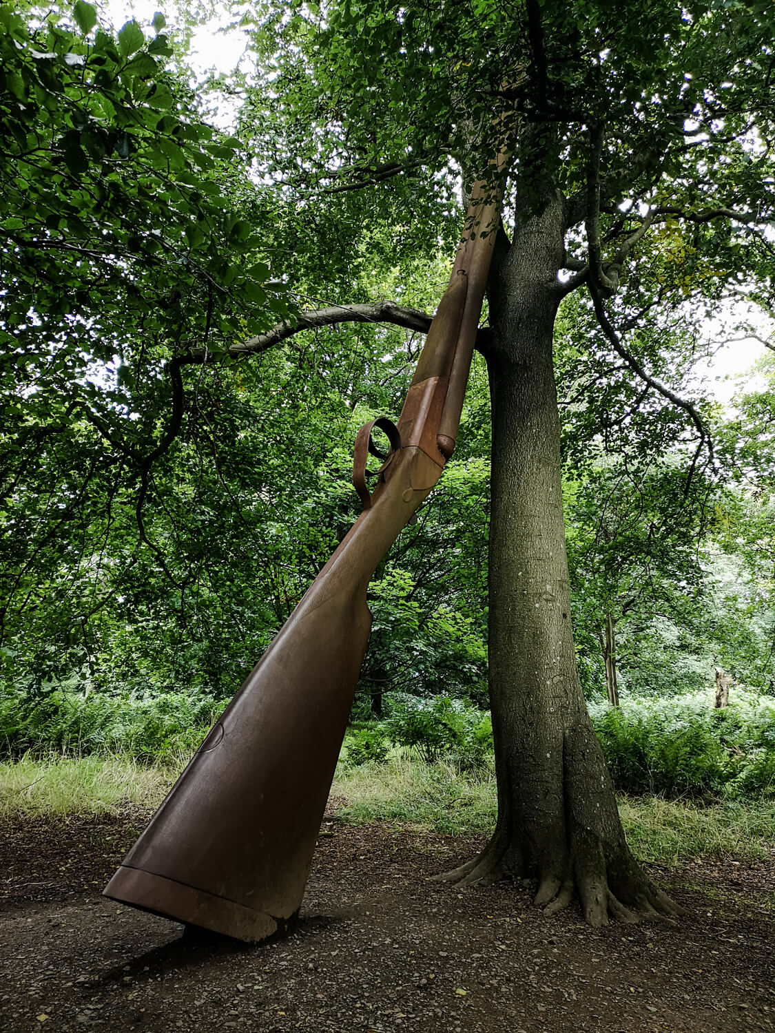 'Landscape with Gun and Tree, 2012' by Cornelia Parker is a giant sculpture of a gun leaning against a tree in Jupiter Artland Edinburgh.