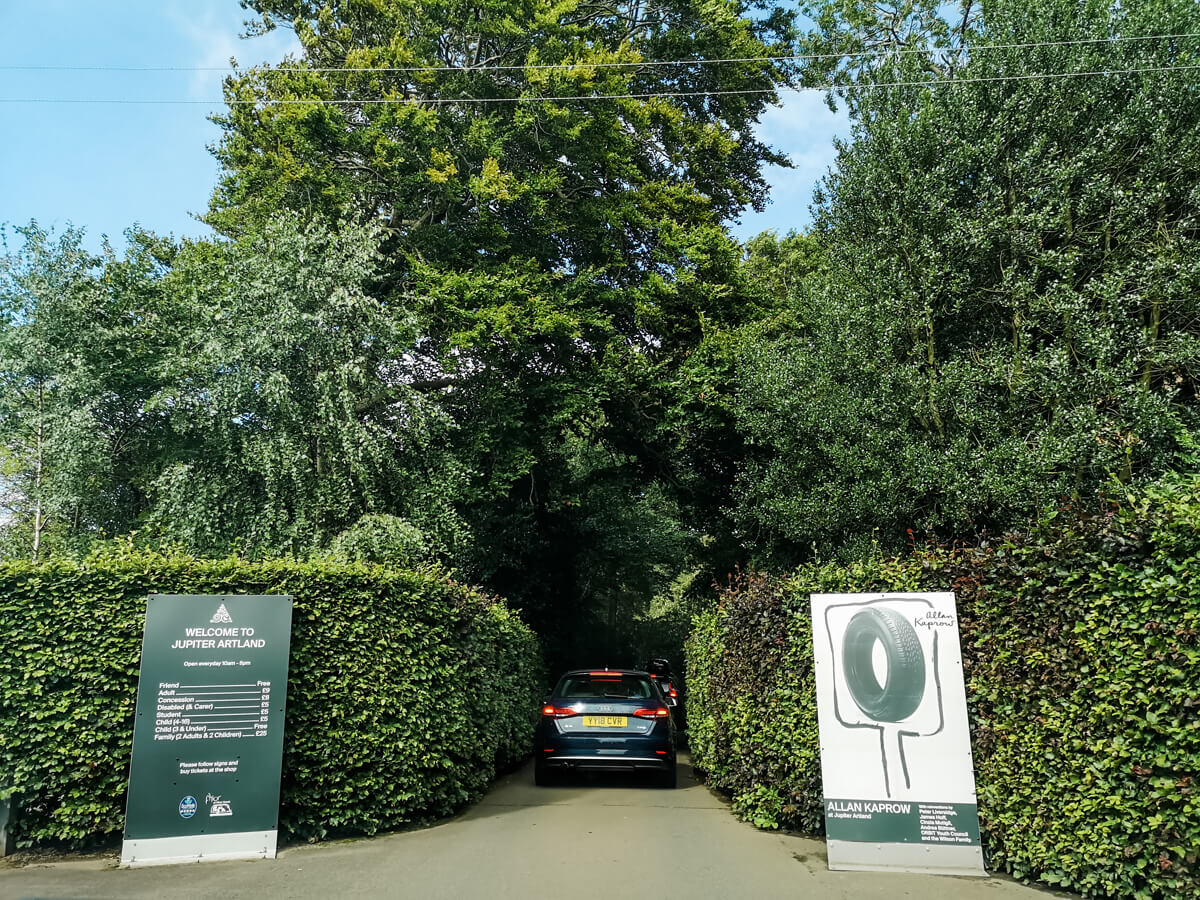 The entrance gates to Jupiter Artland Edinburgh. Tall green hedges line the road with a single track lane with a car driving through.