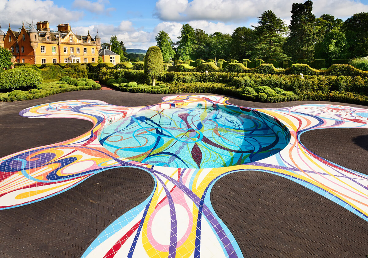 A yellow coloured mansion house in the background and in the forefront is a round swimming pool designed with multicoloured shapes and swirls by Joana Vasconcelos. This installation is called 'Gateway' at Jupiter Artland Edinburgh.
