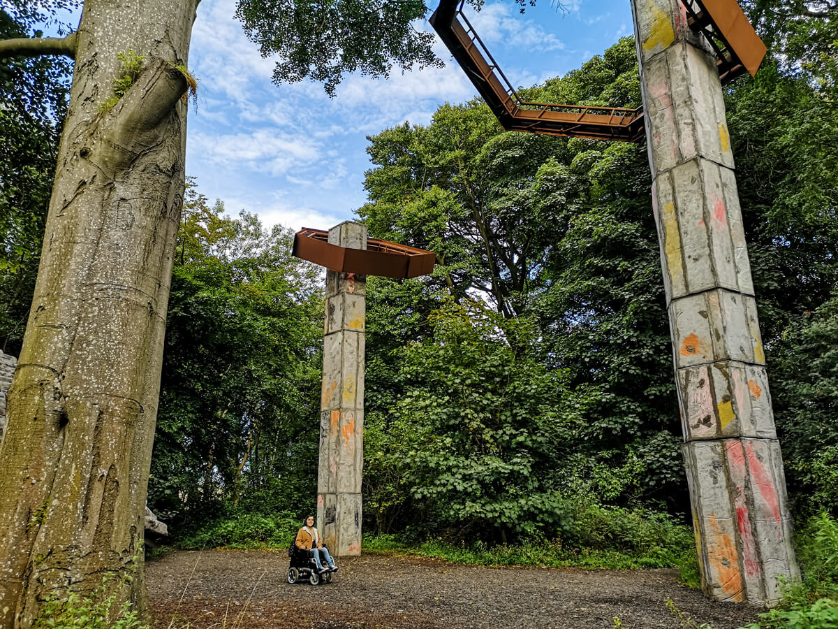 Emma in the woodland surrounded by giant concrete structures of the Quarry art installation at Jupiter Artland Edinburgh.