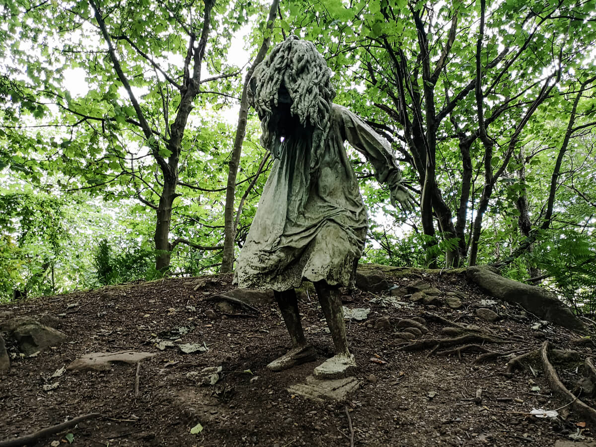 A statue of a weeping girl with her hair covering her face in the middle of the woodland at Jupiter Artland. This art installation is by Laura Ford.