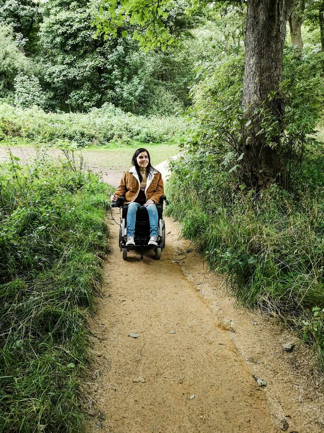 Emma driving her powered wheelchair up a gentle slope path in the woods surrounded by greenery.