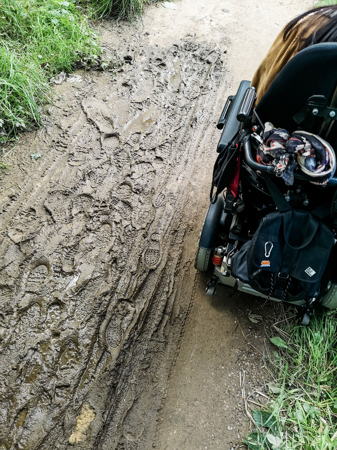 A muddy path in the woodland with Emma driving her wheelchair through it.