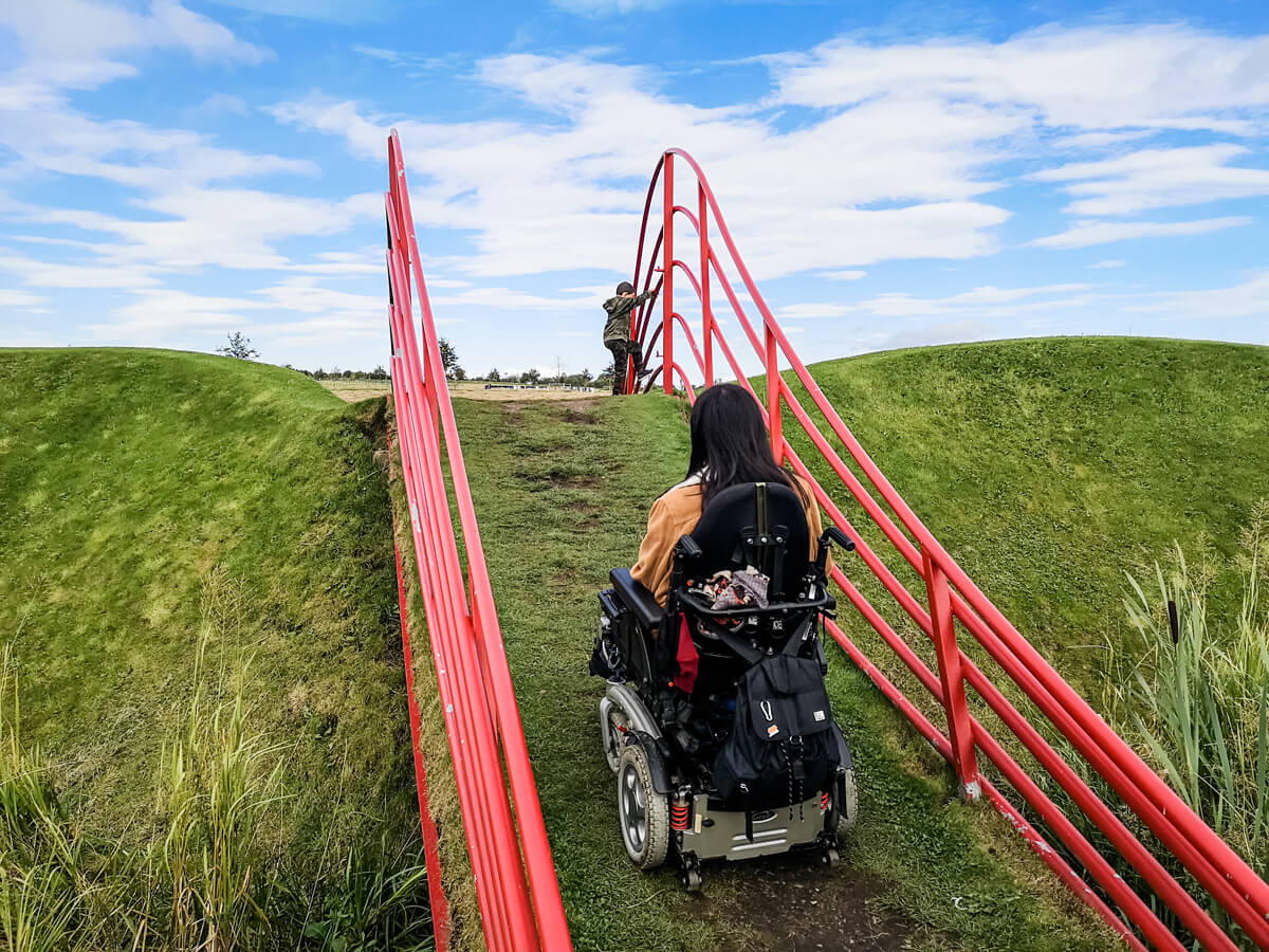 Emma driving up a grassy hill with bridge red railing on each side. Her nephew is waiting for her at the top.