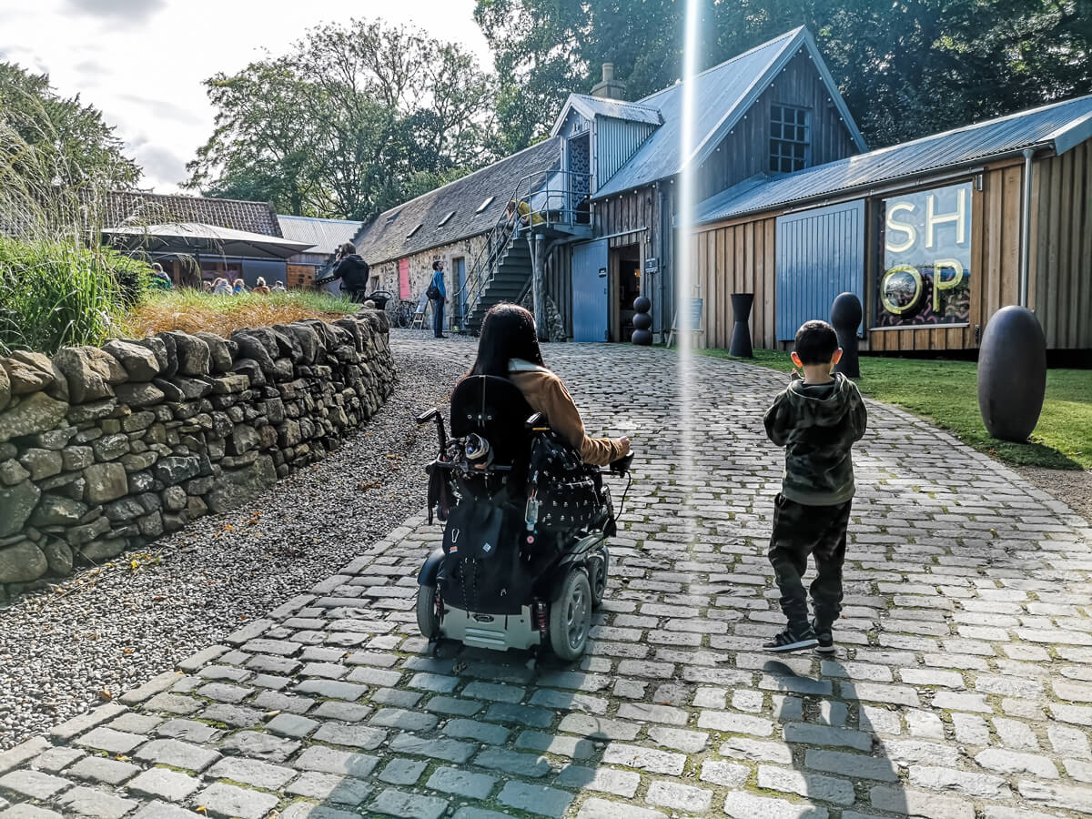 Emma driving her powered wheelchair up a cobblestone slope with her nephew walking beside her. In front of them is a shop and cafe.