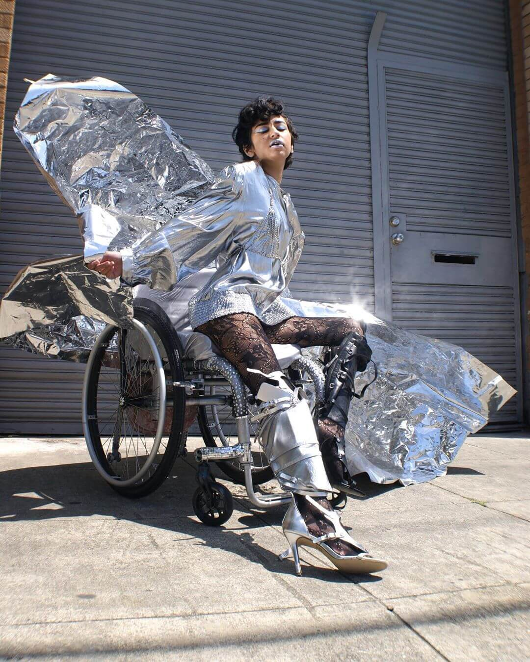 Disabled model Pansy St Battie posing in her manual wheelchair wearing a metallic silver outfit and knee high boots.