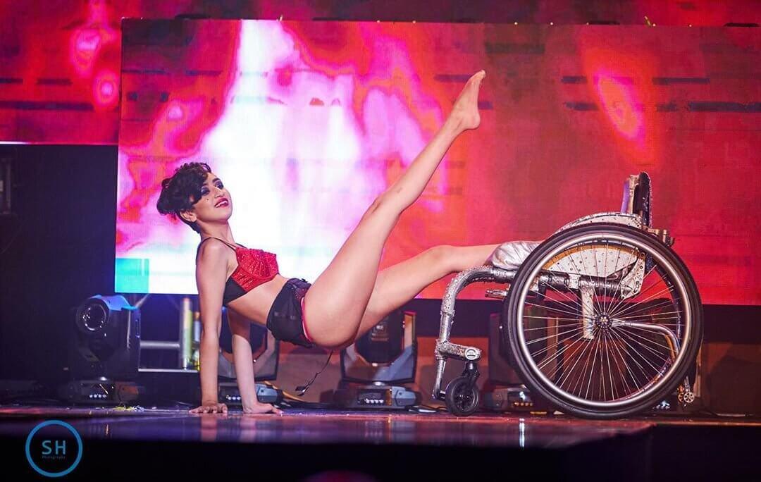 Pansy St Battie during their burlesque performance using their rhinestone decorated wheelchair.