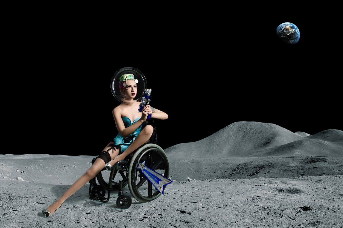 Pansy St Battie sitting in her manual wheelchair during a space themed photoshoot.