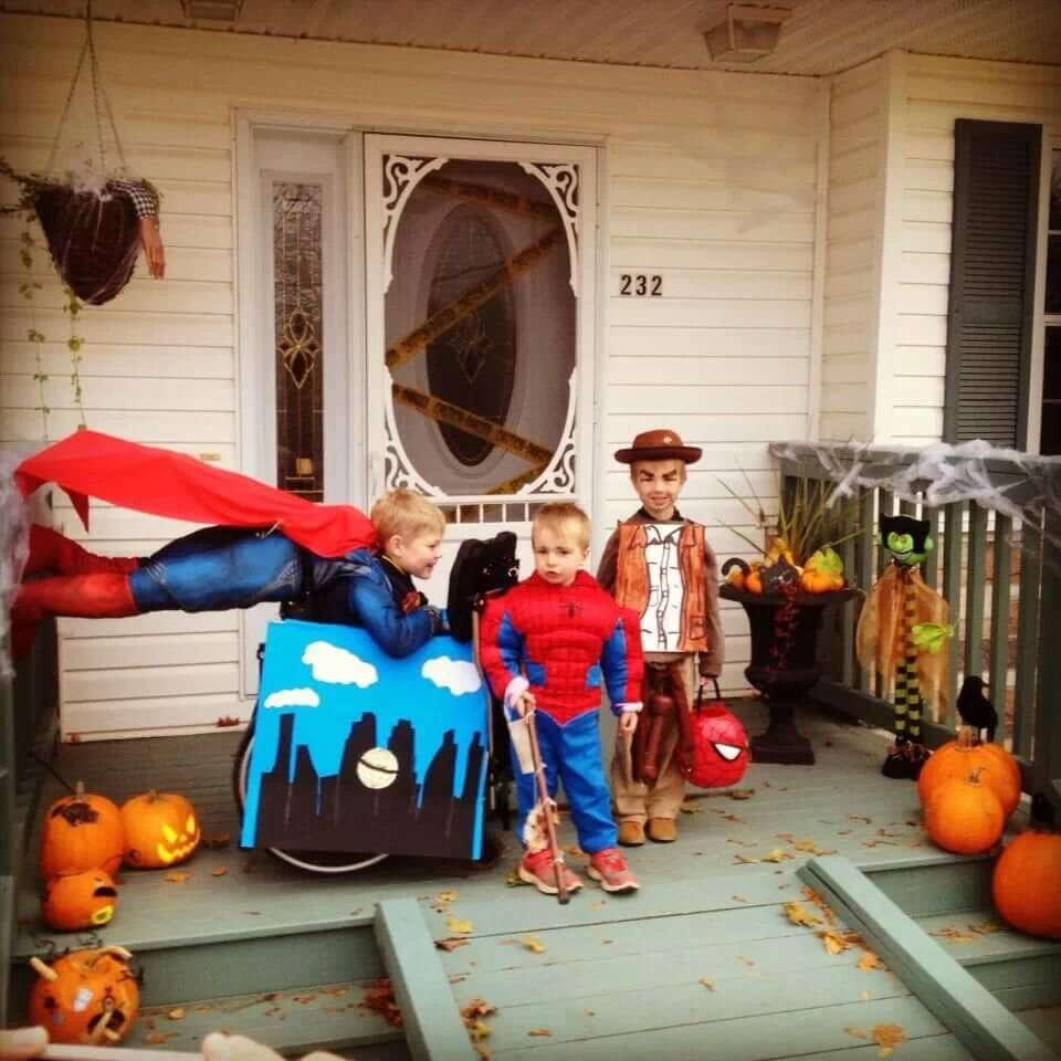 A young boy dressed as Superman. His wheelchair is covered with a City skyline scene. There are Superman legs and cape at the back of his wheelchair to look like he is flying. Two little boys are standing beside him dressed as Spiderman and a Lego Cowboy.