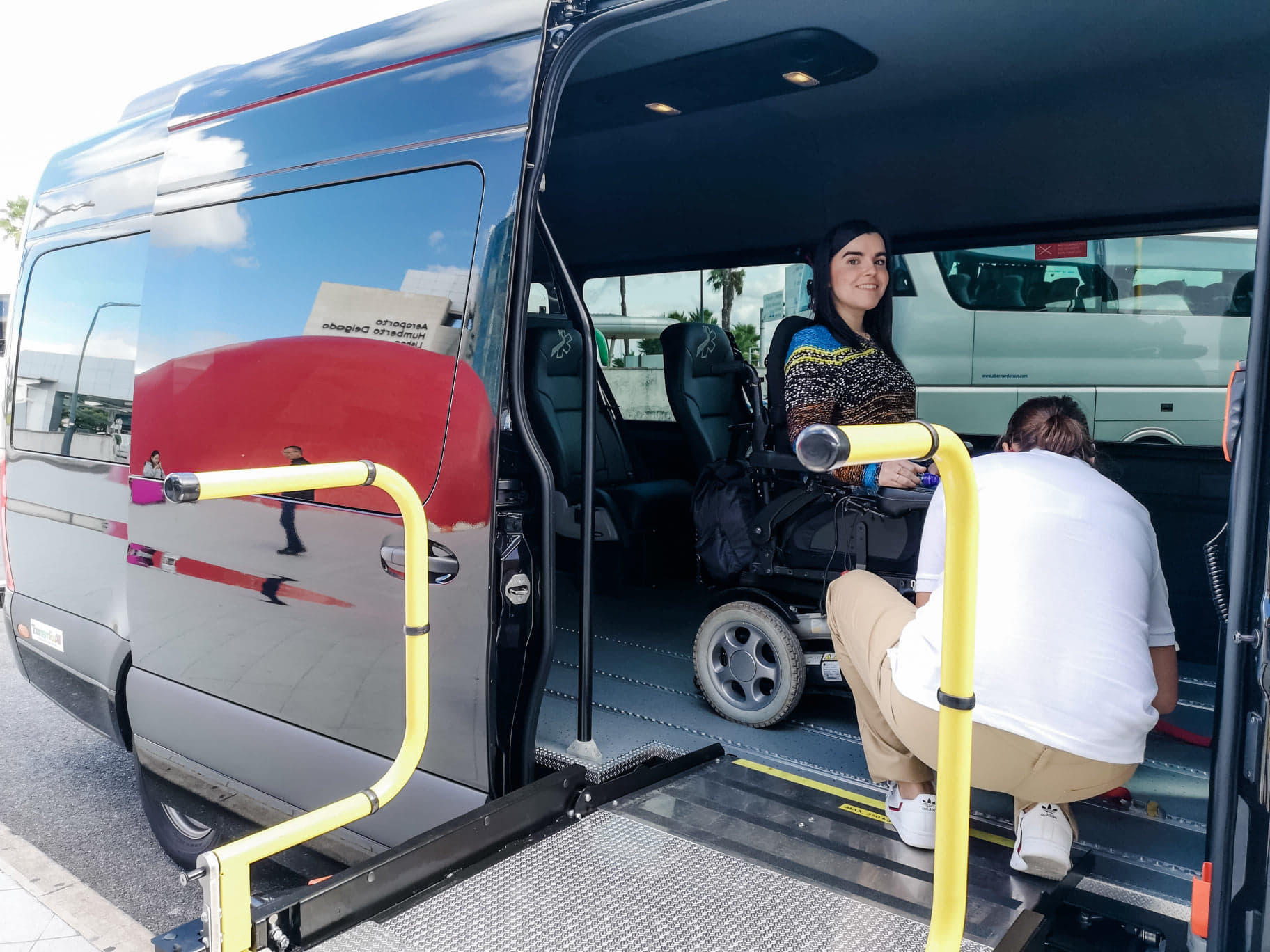 Emma sitting inside a large wheelchair accessible vehicle in her wheelchair. A woman is kneeling down securing Emma's wheelchair to the floor with belts. Emma is smiling.