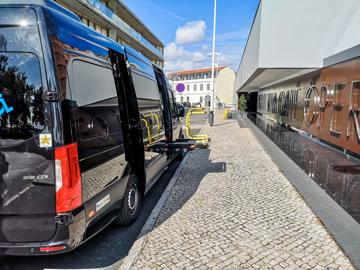 A black wheelchair accessible van from Tourism For All parked outside Vila Gale Opera hote.