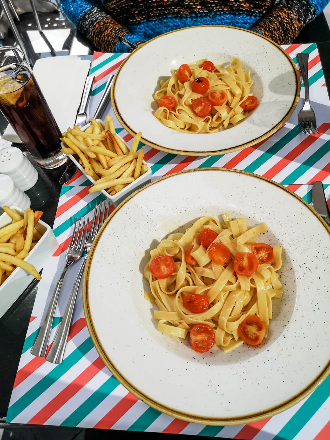 A shot looking down at the table with two dishes of pasta, fries and glasses of coke.