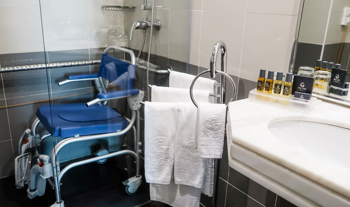 A close up of the shower wheelchair and marble sink.