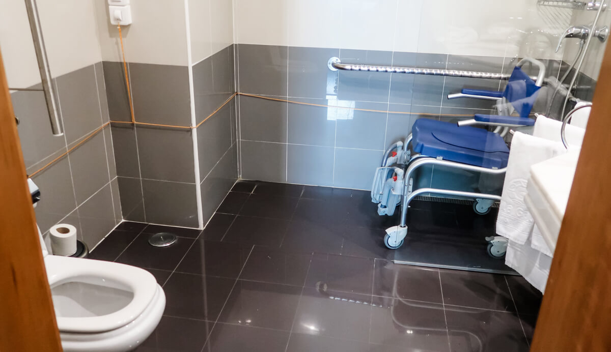 The accessible bathroom at Vila Gale Opera hotel. There is a roll-in shower with a shower wheelchair sitting in it.