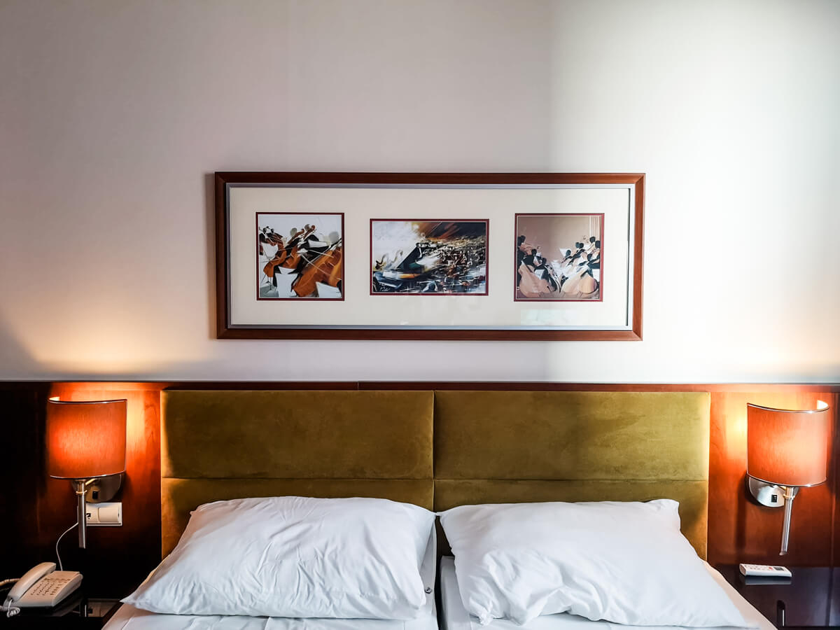 A close up of the bed headboard with a framed photo above the bed.