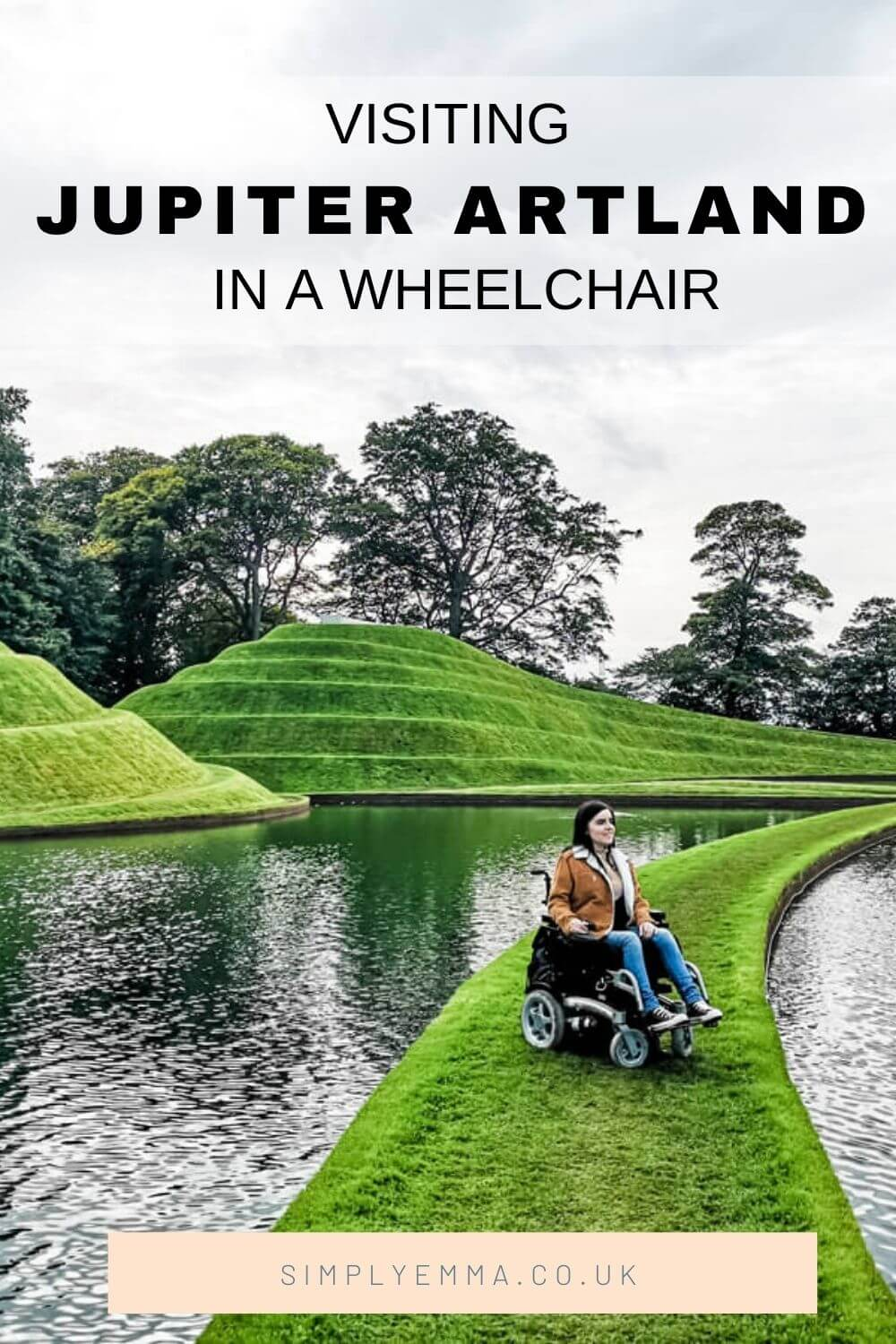 "Emma is sitting in her powered wheelchair on a strip of grass with water on each side of her. Behind her is giant swirly mounds of grass shaped like pyramids. Text reads ""Visiting Jupiter Artland in a wheelchair. Simplyemma.co.uk""."