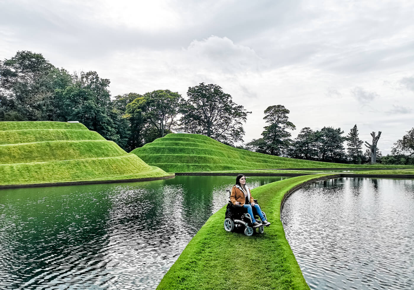 Emma is sitting in her powered wheelchair on a strip of grass with water on each side of her. Behind her is giant swirly mounds of grass shaped like pyramids.