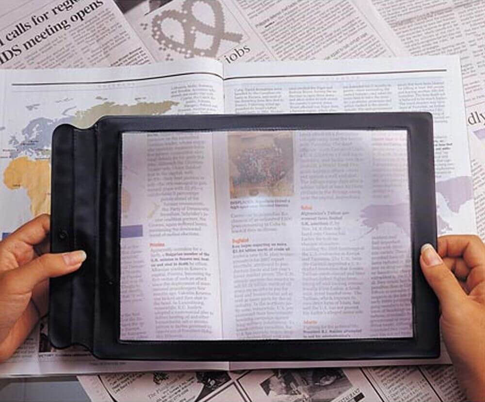 Reading Sheet Magnifier placed over a newspaper. A person is holding the magnifier in their hands.