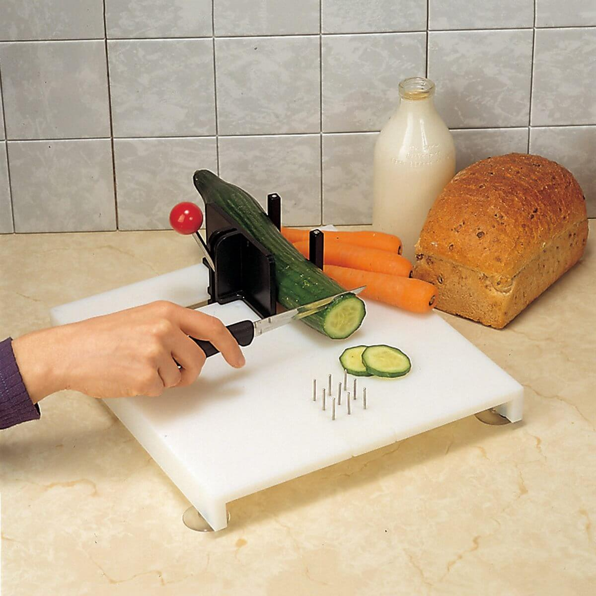 A person's hand holding a knife and cutting vegetables on the Swedish Fix It Food Preparation Board