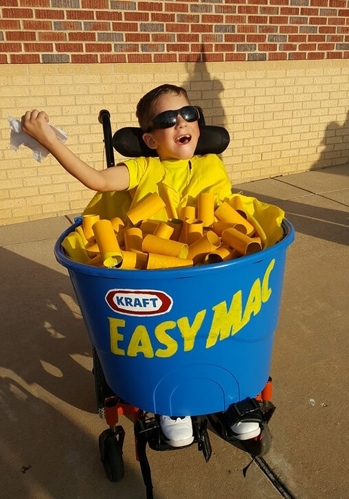 A young boy in a wheelchair dressed up as a bowl of mac and cheese.