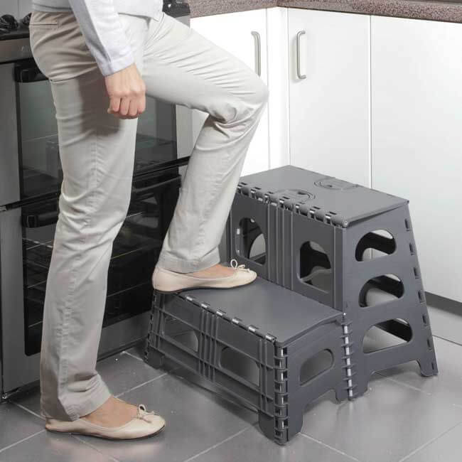 A grey 2-step stool positioned in a kitchen. A womans legs are placed on the first step.