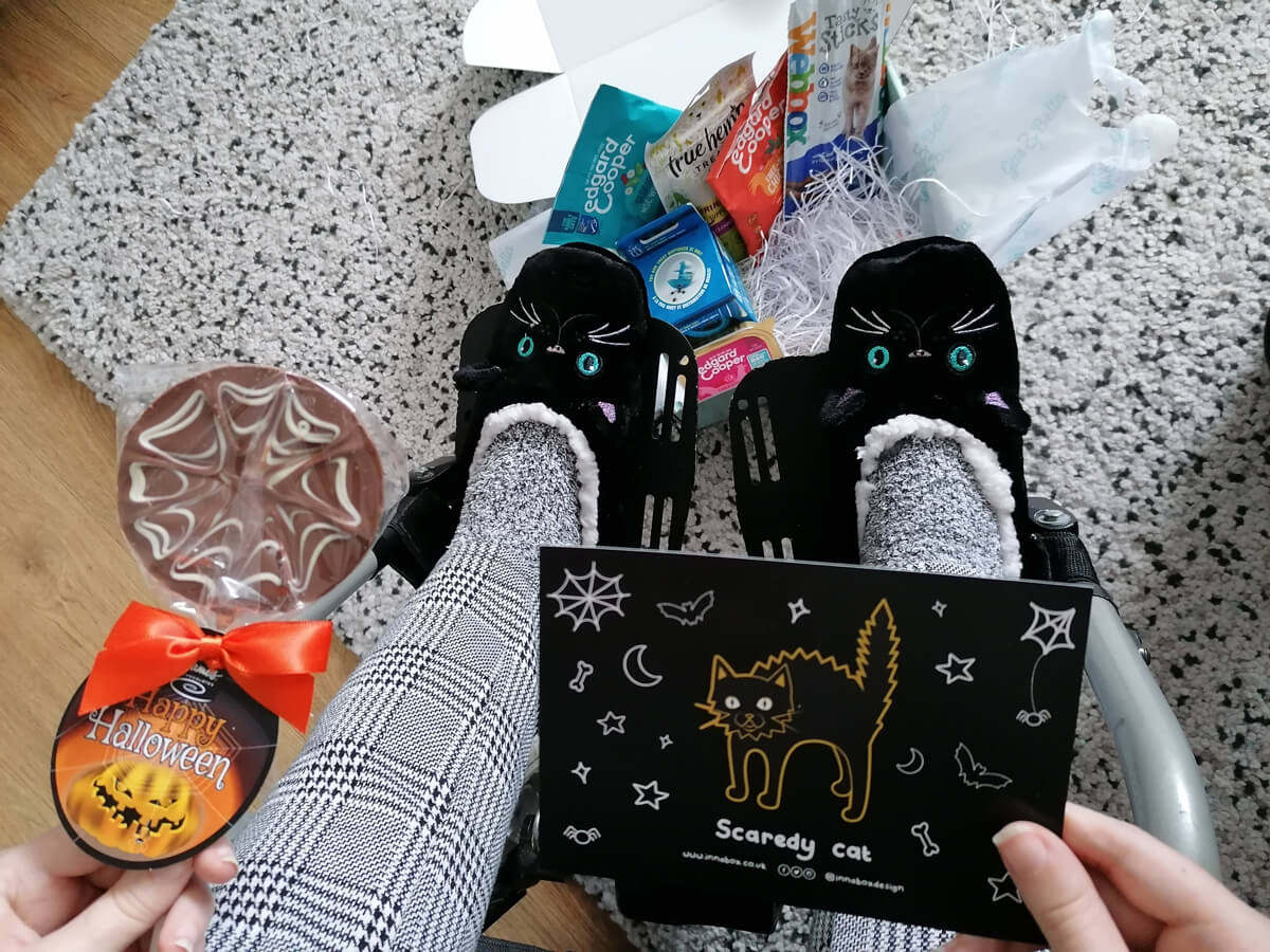 A view looking down at Emma's legs and feet sitting in her wheelchair. Emma is wearing black and white check trousers and fluffy black cat slippers. She is holding a halloween theme chocolate lolly and halloween postcard with a cat design. Laying on the rug at the bottom of Emma's feet is the Gus & Bella cat box.