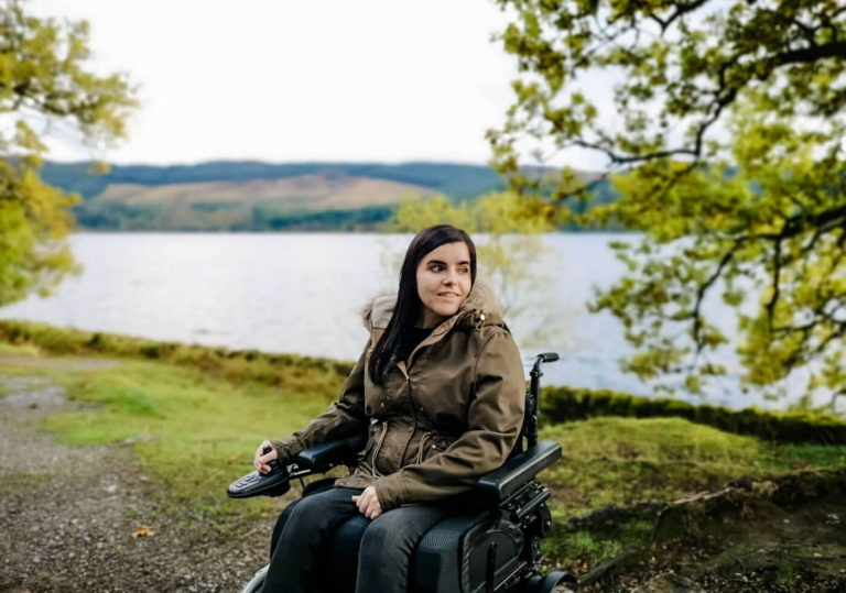 Emma sitting in her wheelchair with Loch Venachar behind her. Hills and trees are also in the background.