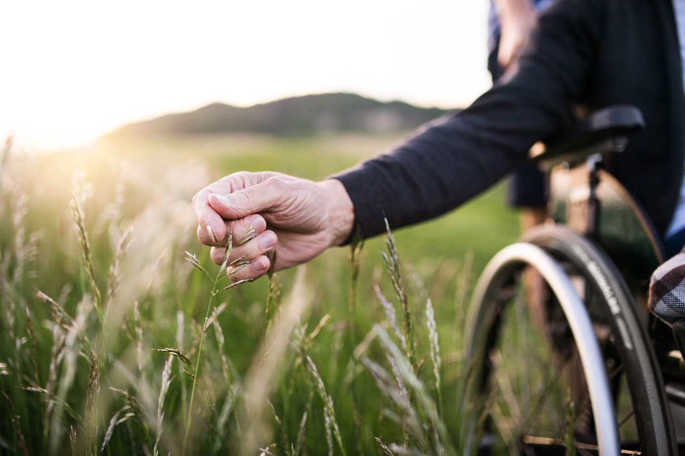 An elderly mans hand reaching out to touch grass while sitting in a wheelchair in the middle of a field.