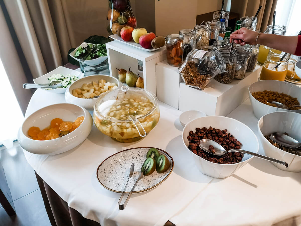 A breakfast buffet table filled with bowls and plates of food.