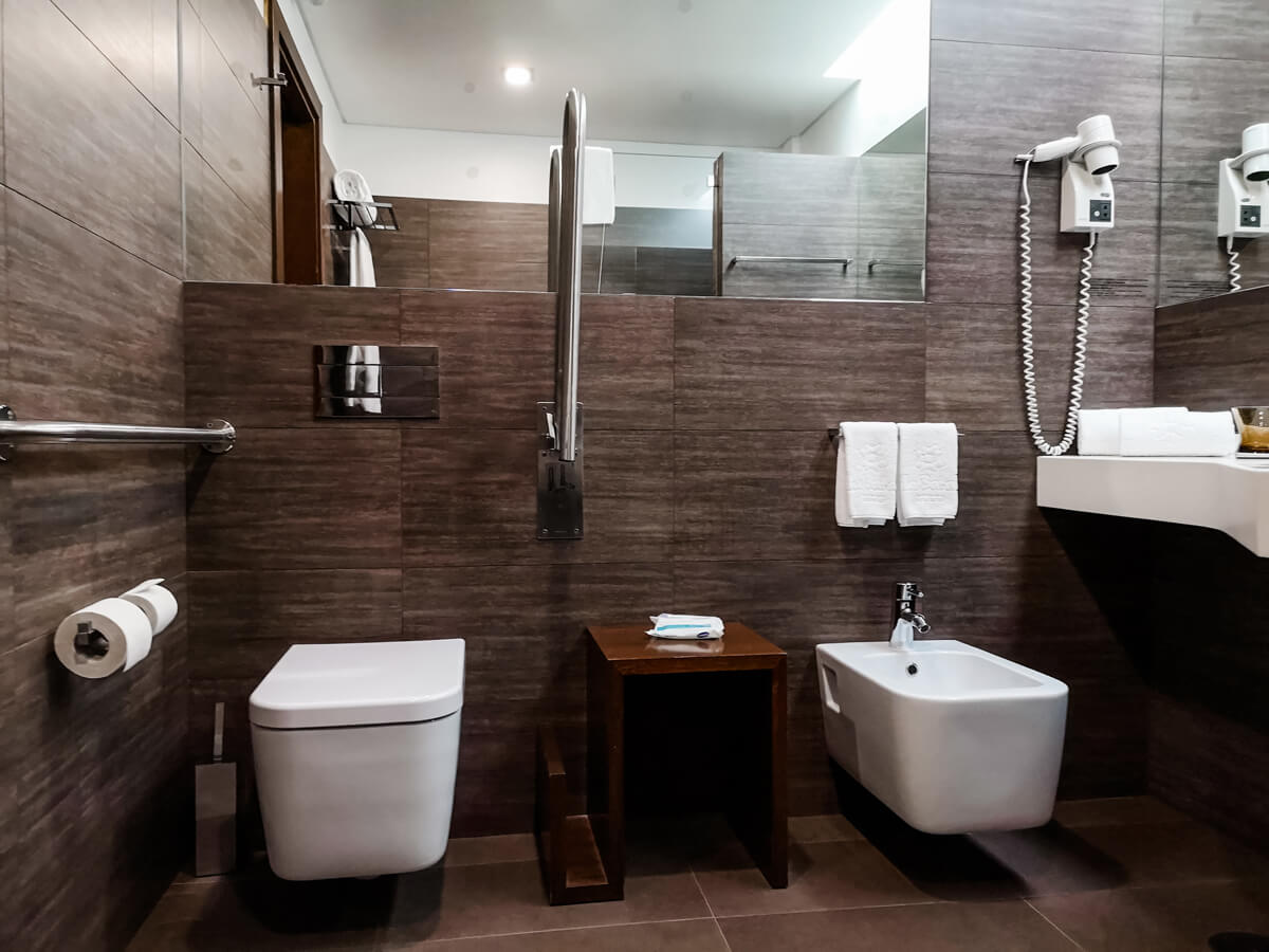 The toilet with grab bars on each side and a bide in the wheelchair accessible bathroom.