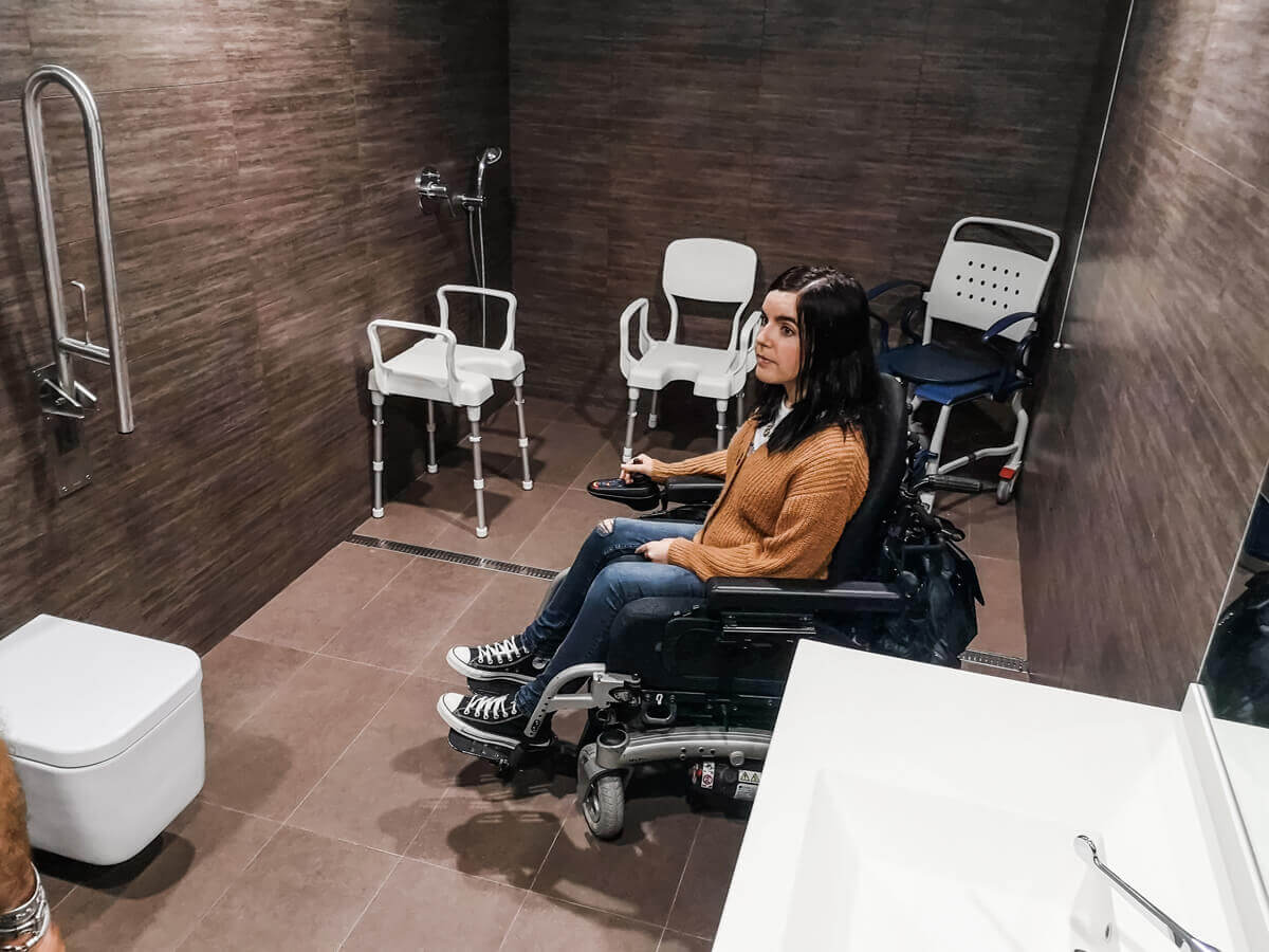 Emma sitting in her wheelchair inside a large accessible bathroom with three different shower seats.