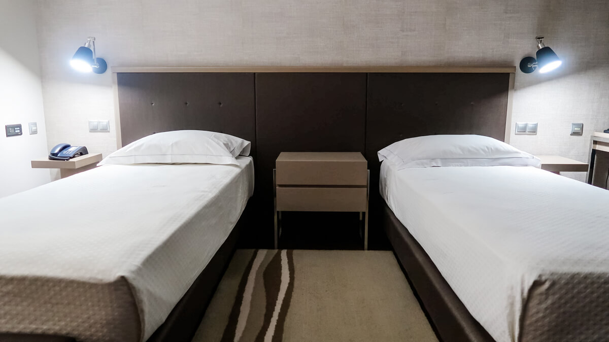 The twin beds in the accessible room at Villa Batalha Hotel. There is a gap between the beds and there is a table placed in the middle of the beds.