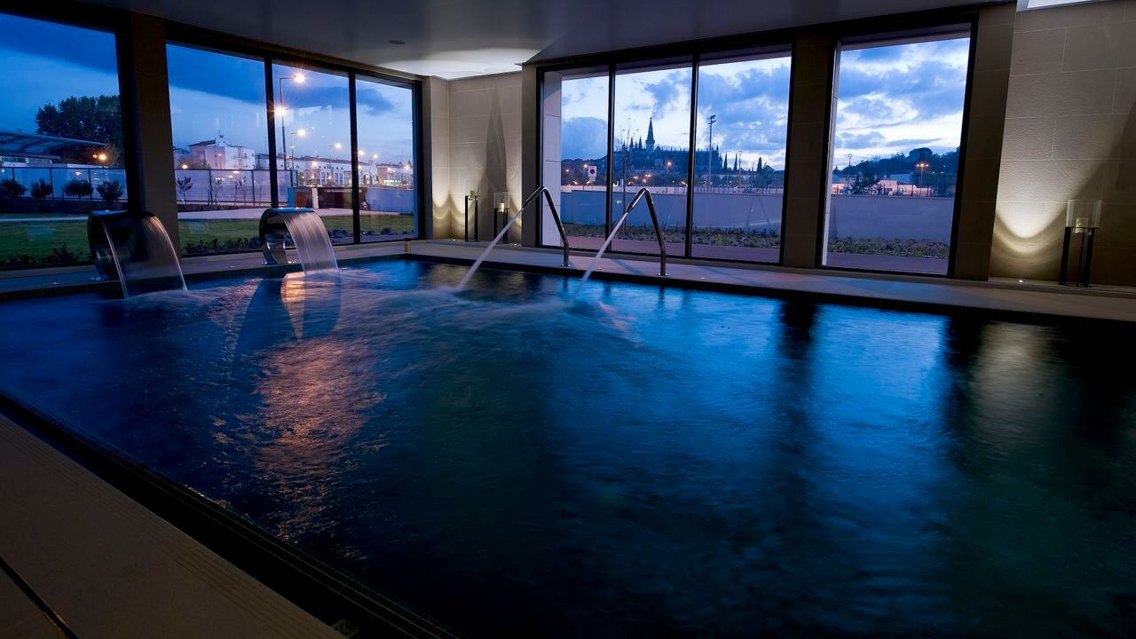 The hotel swimming pool at night with a view of Batalha Monastery in the background through the floor to ceiling windows.