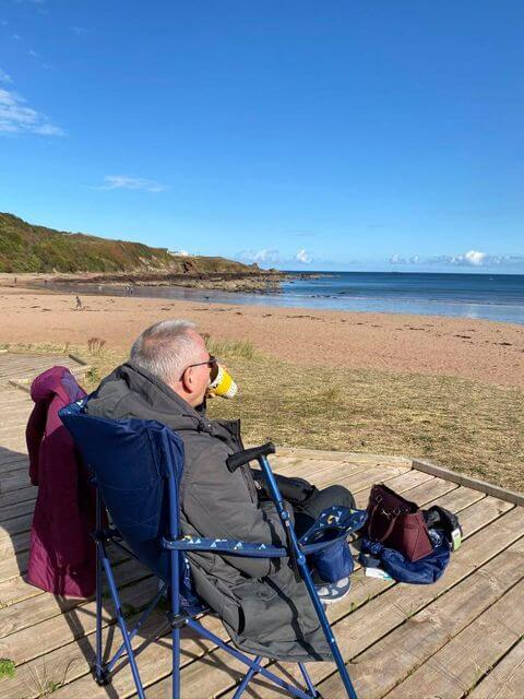 A man sitting on a camping chair at Coldingham Sands Beach eating a picnic overlooking the water.