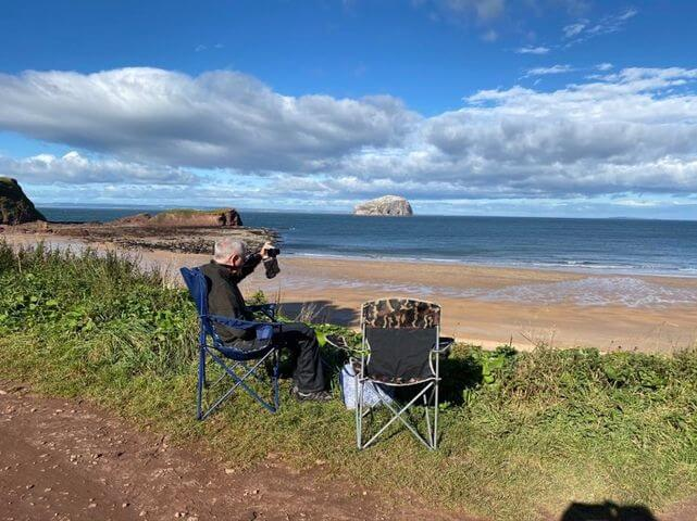 Man sitting on a picnic seat overlooking the water to Bass Rock. It is a sunny day with blue sky and white fluffy clouds.