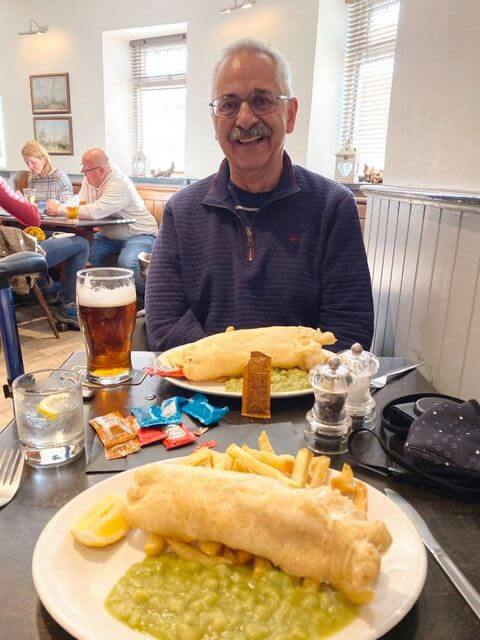 A man sitting at a table eating fish and chips and drinking a beer.