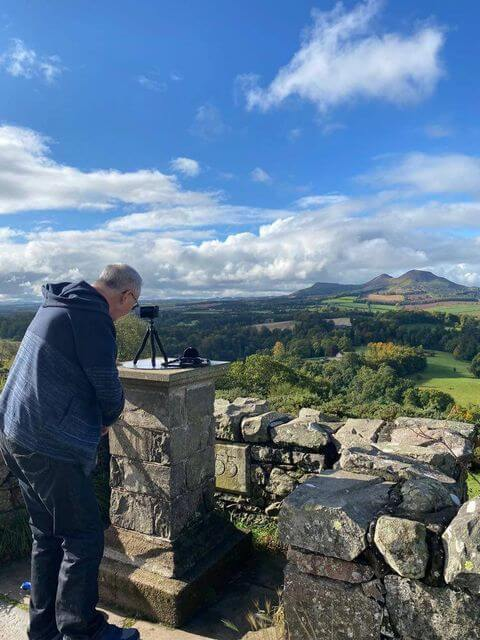 A man standing at the top of Scott's View with his camera enjoying the view across to the Eildon Hills.