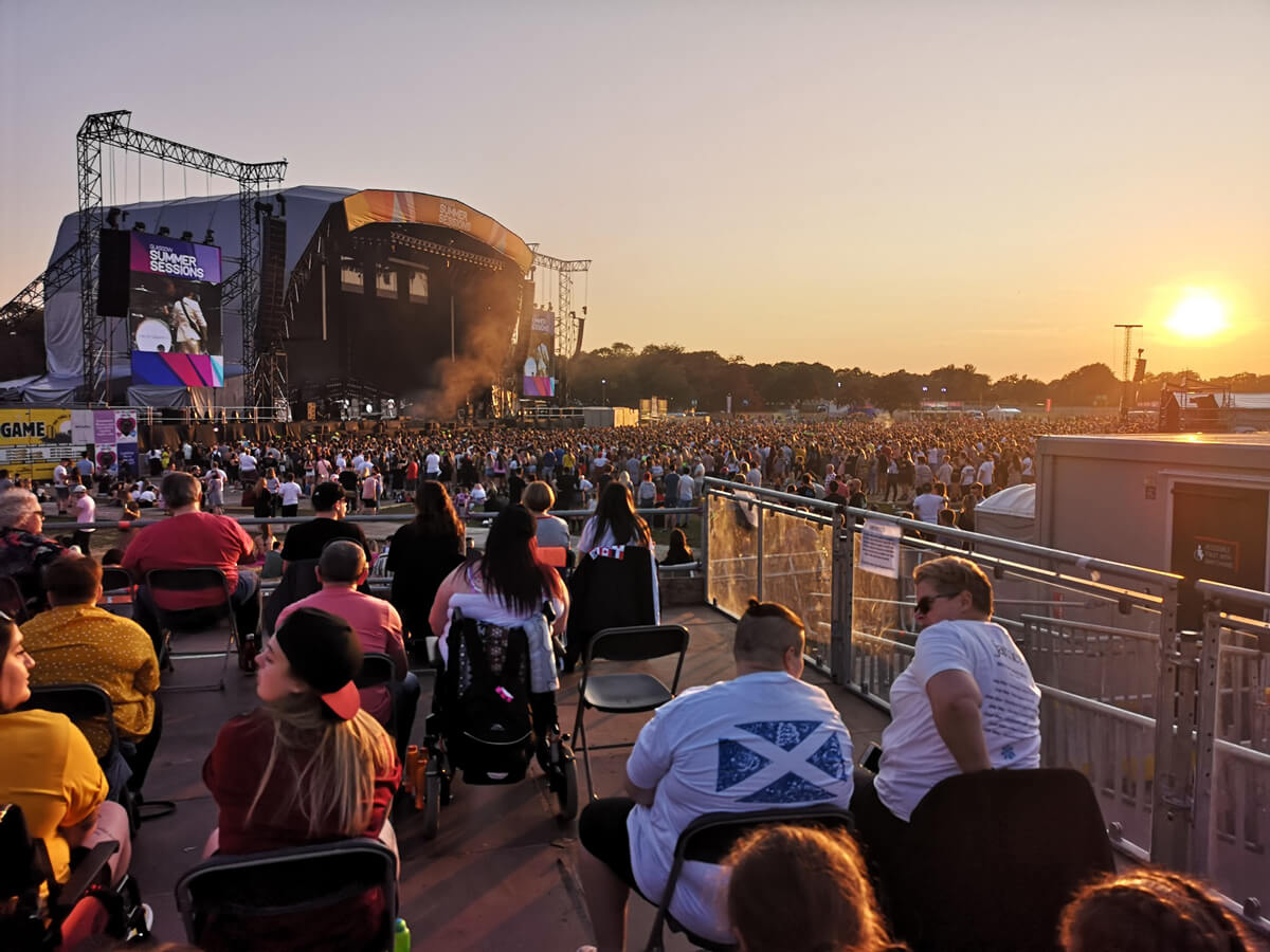 The view of the stage from the accessible viewing platform. There are many people including wheelchair users on the platform. They are at an outdoor music festival.
