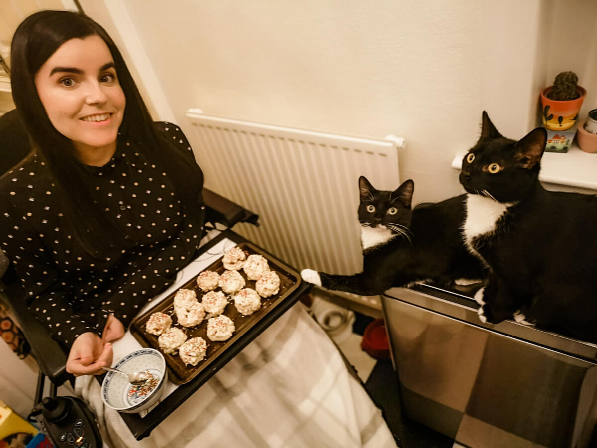 Emma sitting in her wheelchair. She has a white and grey blanket on her legs. She is wearing a black shirt with dots and her long dark hair is down. She has a baking tray with Christmas treats on it as she decorates them. Emma's two black and white cats are sitting on top of a chrome bin watching Emma.