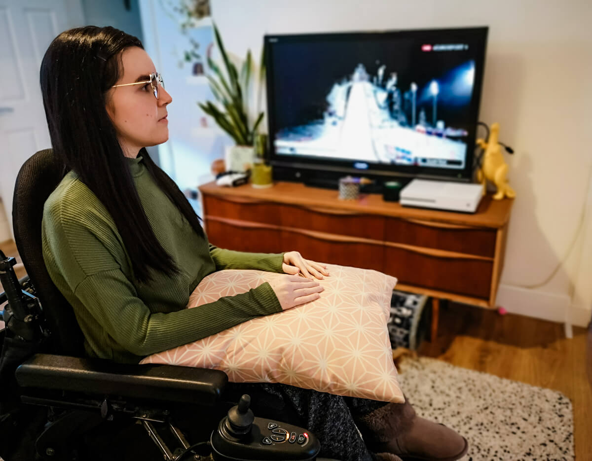 Emma sitting in her wheelchair wearing a khaki coloured top. She is sitting with a peach geometric patterned cushion on her lap which her arms are resting on. The TV is on in the background.