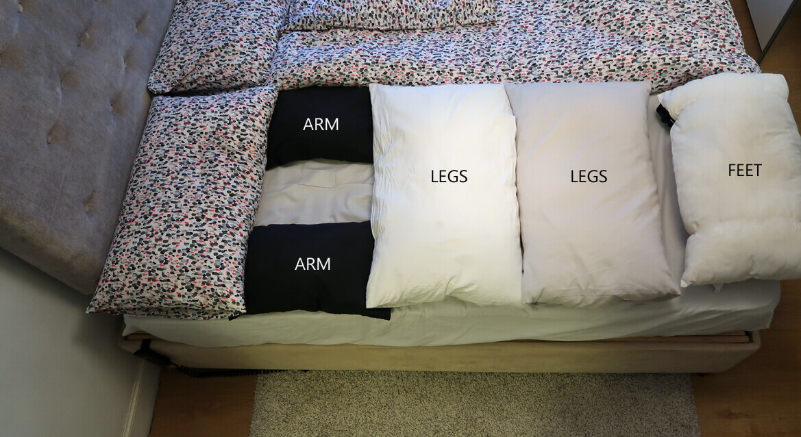A bed with various pillows for supporting the body including arms, legs and feet.