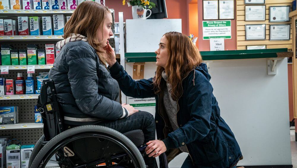 A scene from the movie 'Run' of a mother and daughter. The daughter is a wheelchair user and the mother is bent down to her level with her hand placed on her daughters face. The daughter looks worried.