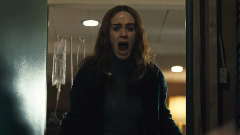 Scene from the movie Run showing actress Sarah Paulson screaming while standing in a door way.