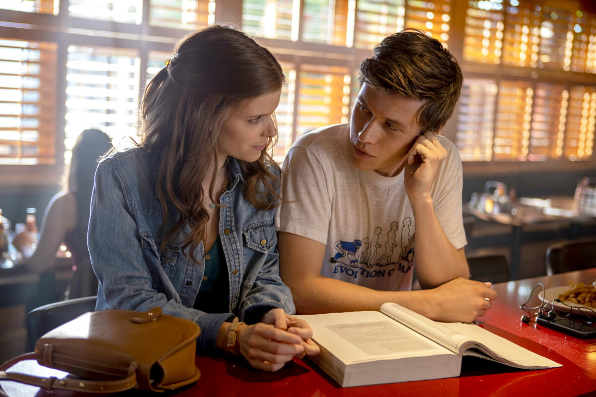A female teacher and male student sitting next to each other in a diner. There are school books on the table in front of them and they are both looking at each in a seductive manner.