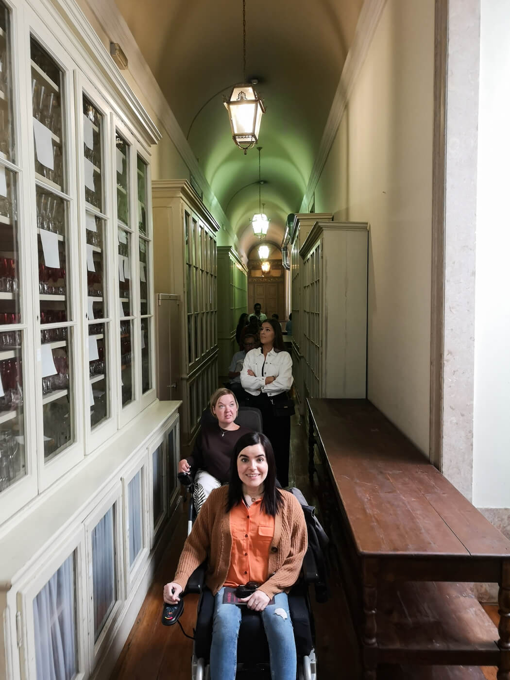 Emma and her friends who are wheelchair users driving through the kitchen porters area at the Ajuda National Palace, Portugal.