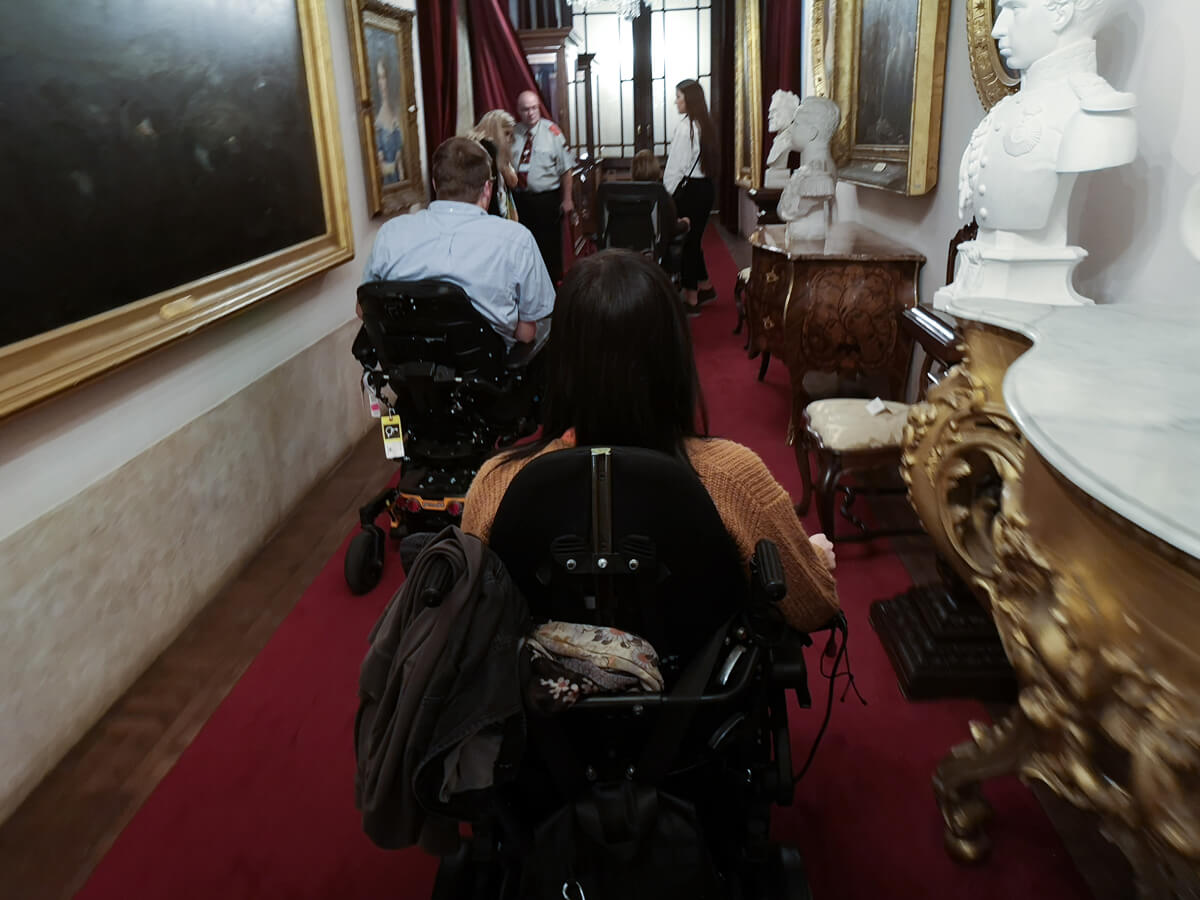 Emma and John (WheelchairTravel.org) driving their wheelchairs through the halls at the Ajuda National Palace, Portugal.