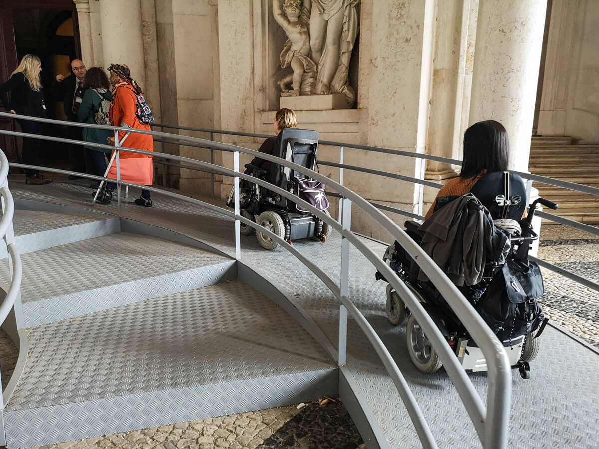 Emma a wheelchair user and her friend who is also a wheelchair user are driving their wheelchairs up the ramp into the Ajuda National Palace, Portugal.
