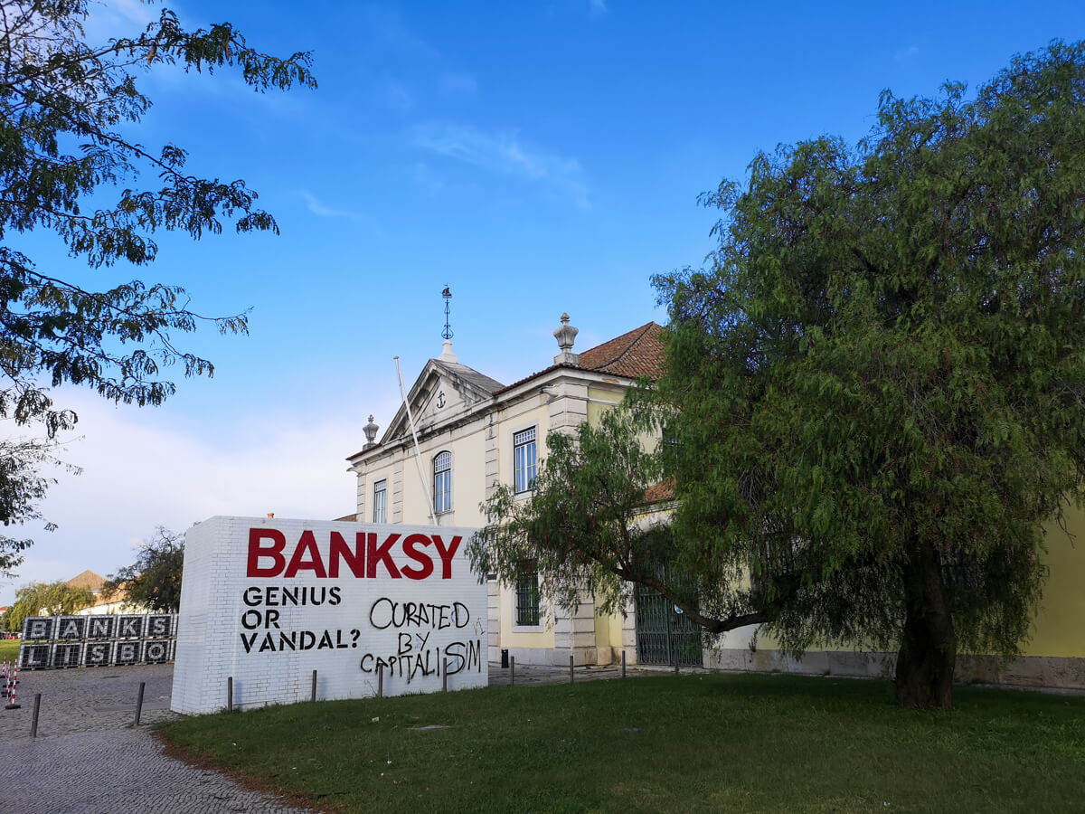 The Cordoaria Nacional in Lisbon. There is a giant sign outside at the entrance. The sign says 'Banksy: Genius or Vandal'.