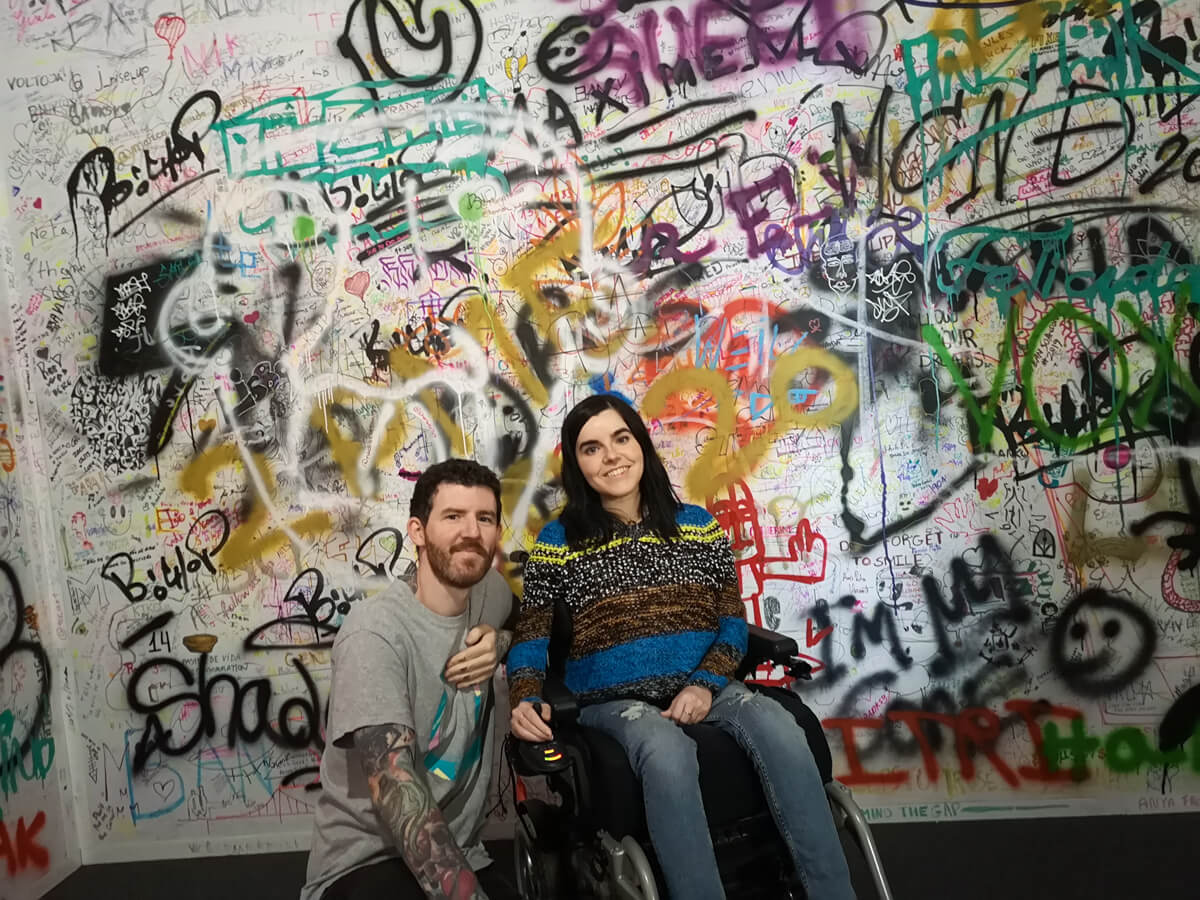 Emma and Allan sitting against a graffiti wall at Banksy: Genius or Vandal exhibition in Lisbon.